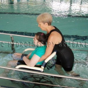 Image of patient being pushed down pool ramp in wheelchair