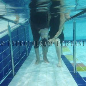 Image of patient walking up pool ramp with knee brace